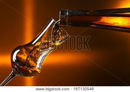 Pouring Alcohol Into A Glass On Dark Background