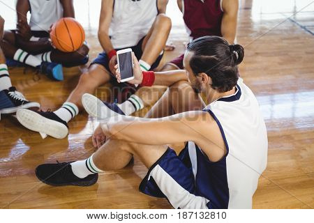 Basketball player using mobile phone while relaxing in the court