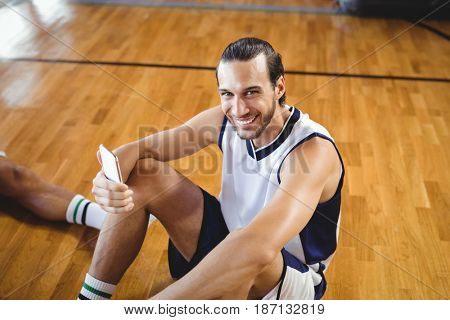 Portrait of smiling basketball player using mobile while relaxing in court