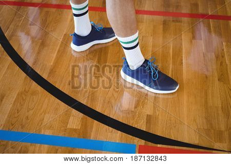 Low section of basketball player standing in the court