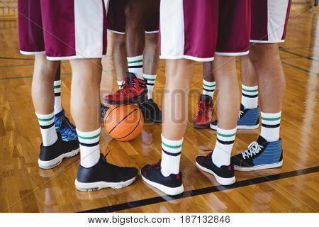 Low section of basketball players forming a huddle in the court