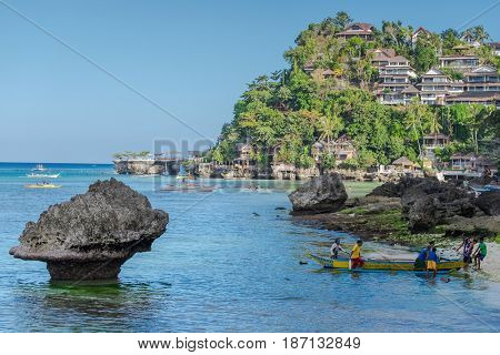Boracay, Philippines - March 14, 2016: Fishermen and boats  at famous Diniwid Beach on Boracay Island, Philippines