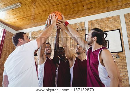 Smiling players and coach holding basketball together in the court