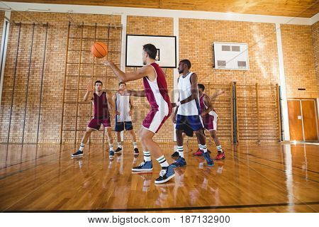 Determined basketball players playing in the court