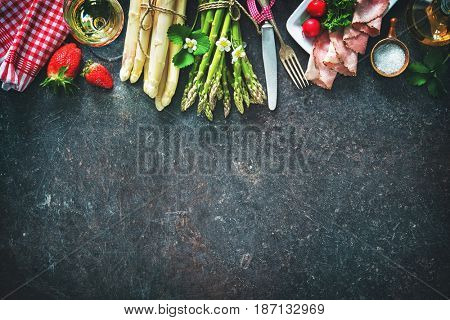 Fresh green and white asparagus with strawberries and wineglas on dark background