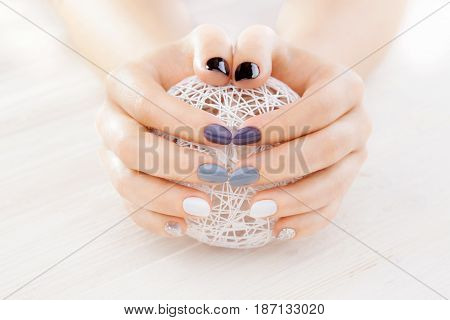 gray manicure with a white ball of yarn on the white wooden table.