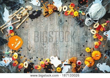 Halloween holiday background with skull, skeleton, spiders, pumpkins and candy. View from above