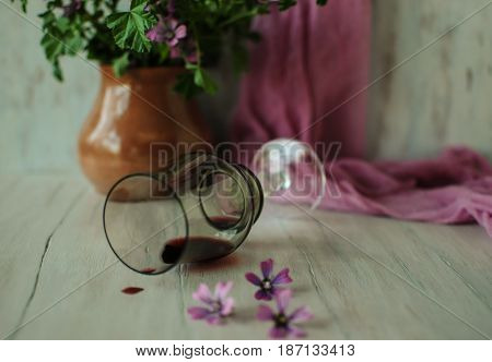Lying glass with the remains of wine and a drop on the table.