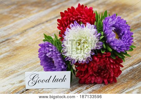 Good luck card with colorful aster flowers bouquet on rustic wooden surface