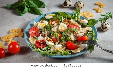 Farfalle bow tie pasta salad with quail eggs, cherry tomatoes, rucola, mozzarella and basil, dressed with balsamic sauce over grey concrete background