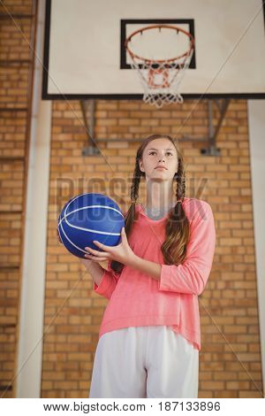 Determined girl holding a basketball in the court