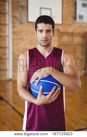Portrait of determined basketball player holding a basketball in the court