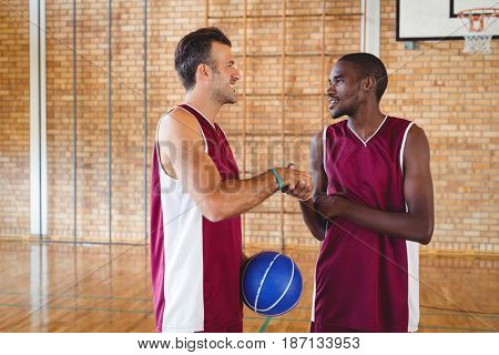 Smiling basketball players shaking hands with each other in the court