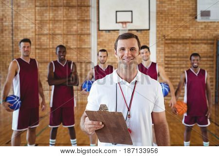 Portrait of smiling coach and basketball player standing in the court