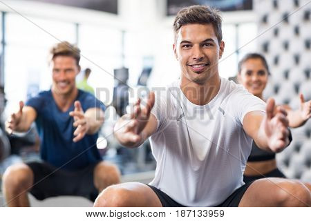 Group of happy people exercising in squat position. Man doing stretching exercise and looking at camera. Portrait of smiling personal trainer doing squat exercise with fitness class in background.