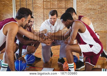 Basketball player and coach forming a handstack in the court