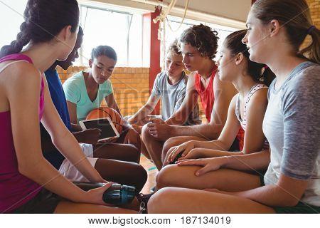 High school kids using digital tablet in basketball court