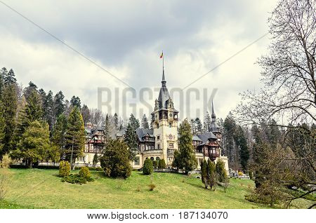 The Peles Castle From Sinaia Romania, Gardens With Green Grass And Trees