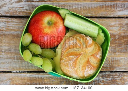Packed lunch containing cheese roll, red apple, grapes and cucumber sticks