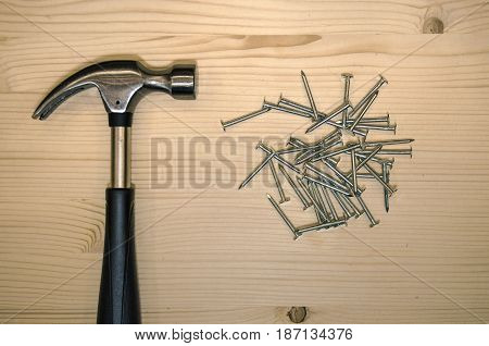 Hammer and nails. Hammer and nails on wooden desk table.