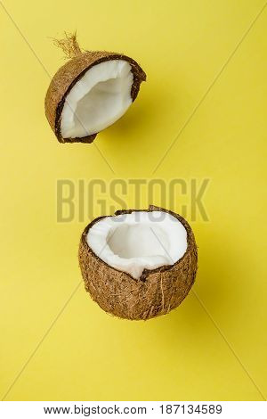 Coconut on yellow colored background minimal flat lay style