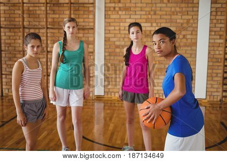 Portrait of high school kids standing with basketball in the court