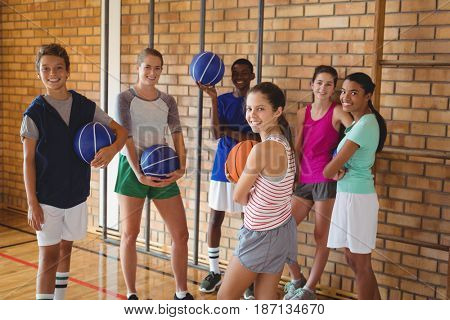 Portrait of happy high school kids standing with basketball in the court