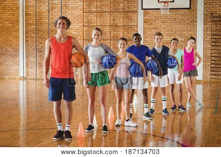 Portrait of smiling high school team holding basketball in the court
