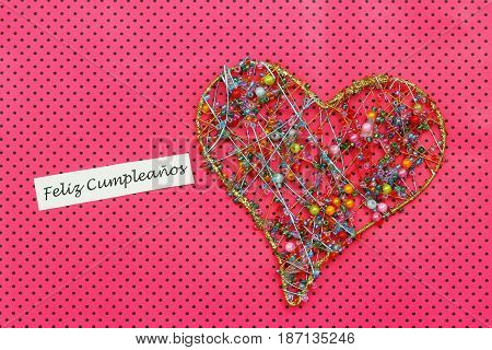 Feliz Cumpleanos (which means Happy Birthday in Spanish) card with heart made of colorful beads on dotty pink surface