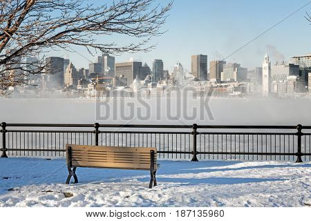 A view across the St Lawrence river to downtown Montreal. Winter shot with snow on the ground and mist rising from the frozen water.