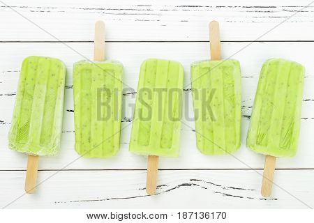 Homemade vegan green tea matcha mint coconut milk popsicles - ice pops - paletas with chia seeds on rustic white wooden background