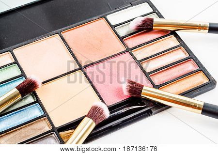 Crushed blush and eyeshadow makeup in set palette with brush on white background.