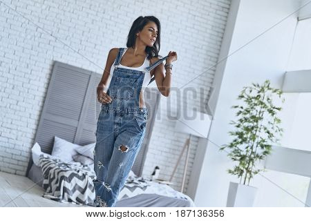 Irresistible girl. Attractive young woman touching her bib overalls and looking away while walking in the bedroom at home