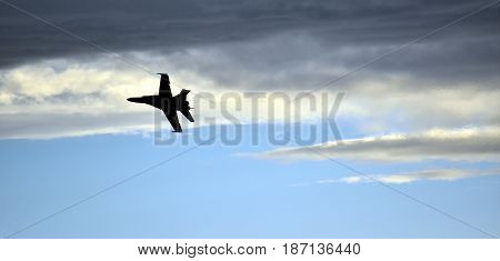 Silhouette of F18 Hornet fighter aircraft in flight. Clouds in the background.