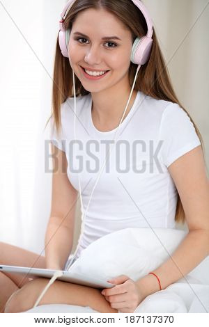 Woman listening music in bed with pink headphones after wake up, entering a day happy and relaxed after good night sleep. Sweet dreams, good morning, new day, weekend, holidays concept.