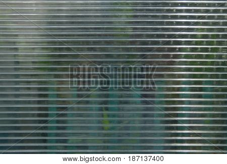 Polycarbonate surface with green objects behind. Geometric background.