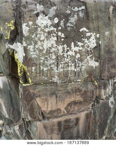 Aged stone with moss and cracks. Rock painting of deer at the bottom. Natural background, solid surface with ancient arts.