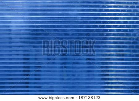 Blue polycarbonate surface with  objects behind.  Industrial background, regular structure with horizontal structure. Plastic texture with place for text.