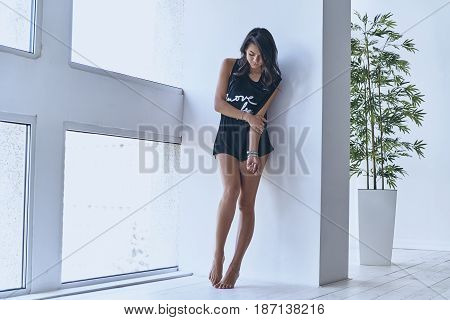 Gorgeous beauty. Full length of beautiful young woman keeping eyes closed while leaning on the wall near the window