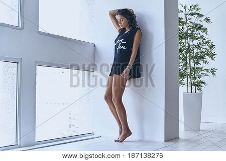 Thoughtful beauty. Full length of beautiful young woman keeping hand behind head while leaning on the wall near the window