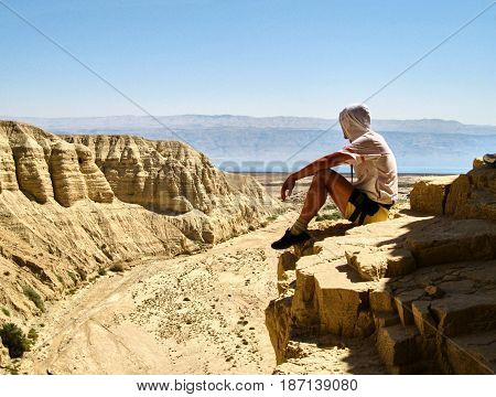 Man Sits On A Ledge. Canyon Ein Avdat In Negev Desert