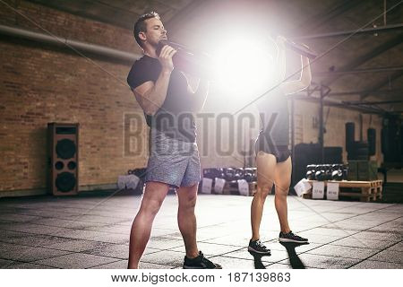 Young Athletic Sportspeople Lifting Weights In Gym