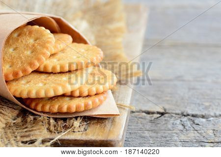 Salty crispy crackers in a wrapping paper and on a sackcloth. Vintage wooden background with copy space for text. Tasty crackers snack idea for kids and adults