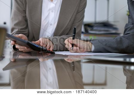 Two female accountants counting on calculator income for tax form completion, hands closeup. Internal Revenue Service inspector checking financial document. Planning budget, audit  concept.