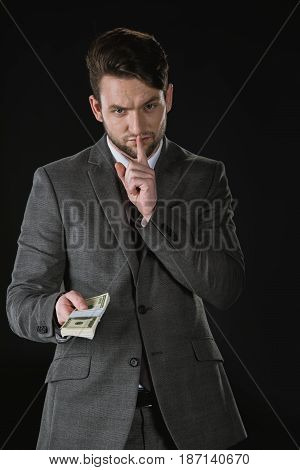 Young Businessman With Hush Gesture Holding Dollar Banknotes Isolated On Black
