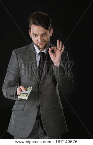 Young Businessman Holding Dollar Banknotes And Showing Ok Sign Isolated On Black