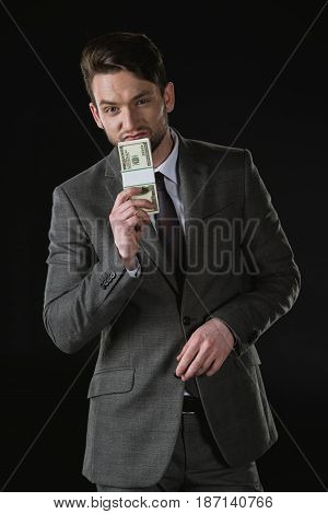 Young Businessman Holding Dollar Banknotes Isolated On Black