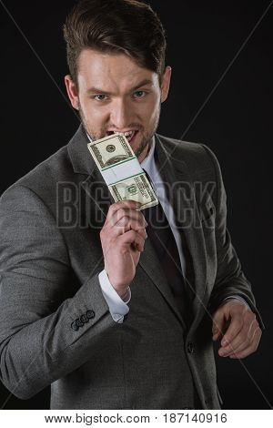Young Businessman Biting Dollar Banknotes Isolated On Black