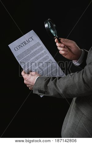 Partial View Of Businessman Reading Contract Through Magnifying Glass Isolated On Black
