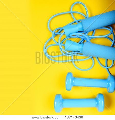 skipping rope and blue dumbbells on yellow background copy space